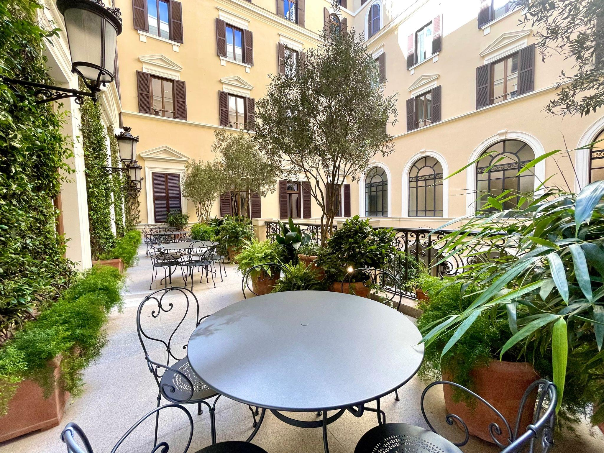The terrace overlooks the courtyard and features jasmine vines and olive trees inspired by Roman roof terraces.